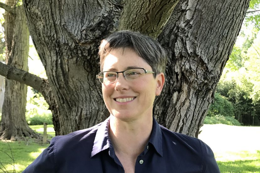 A smiling woman wearing a dark blue shirt stands in front of tree. A bright patch of sun is visible in the grass behind her.