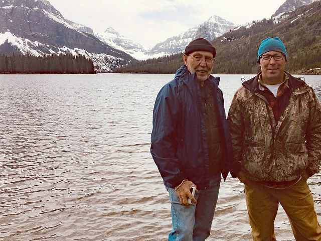 Two men in pose in front of a mountain lake.
