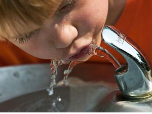 Young boy getting a drink of clean water from the drinking fountain.