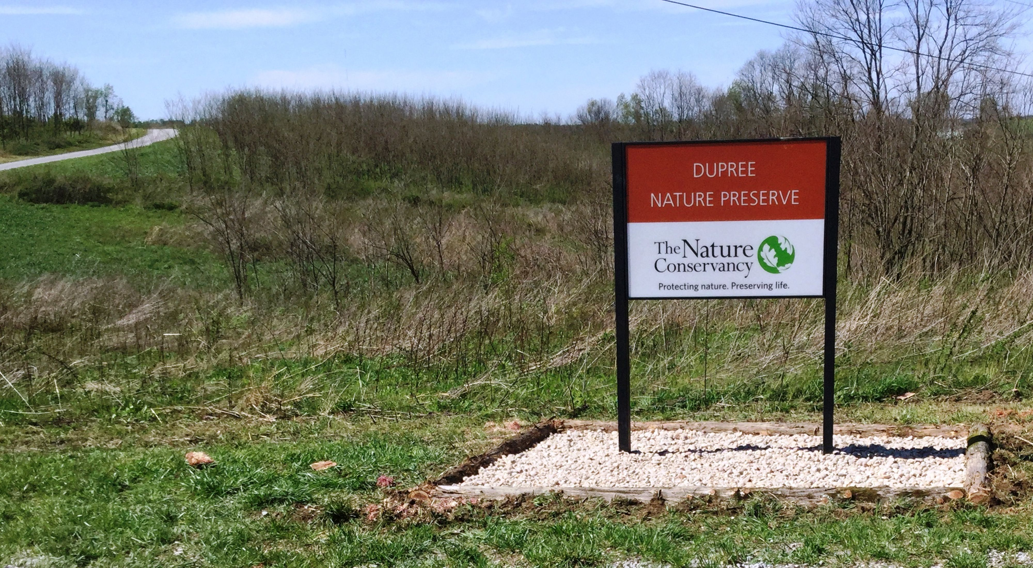 A brown and white sign marks a nature preserve.