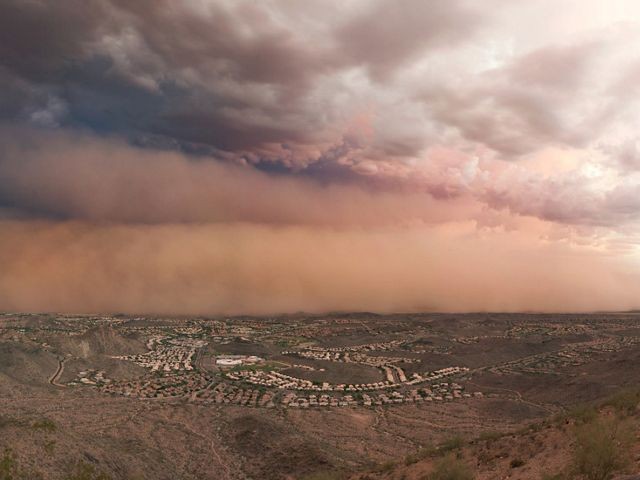 Gray and pink dust clouds over buildings in the distance near Phoenix, Arizona.
