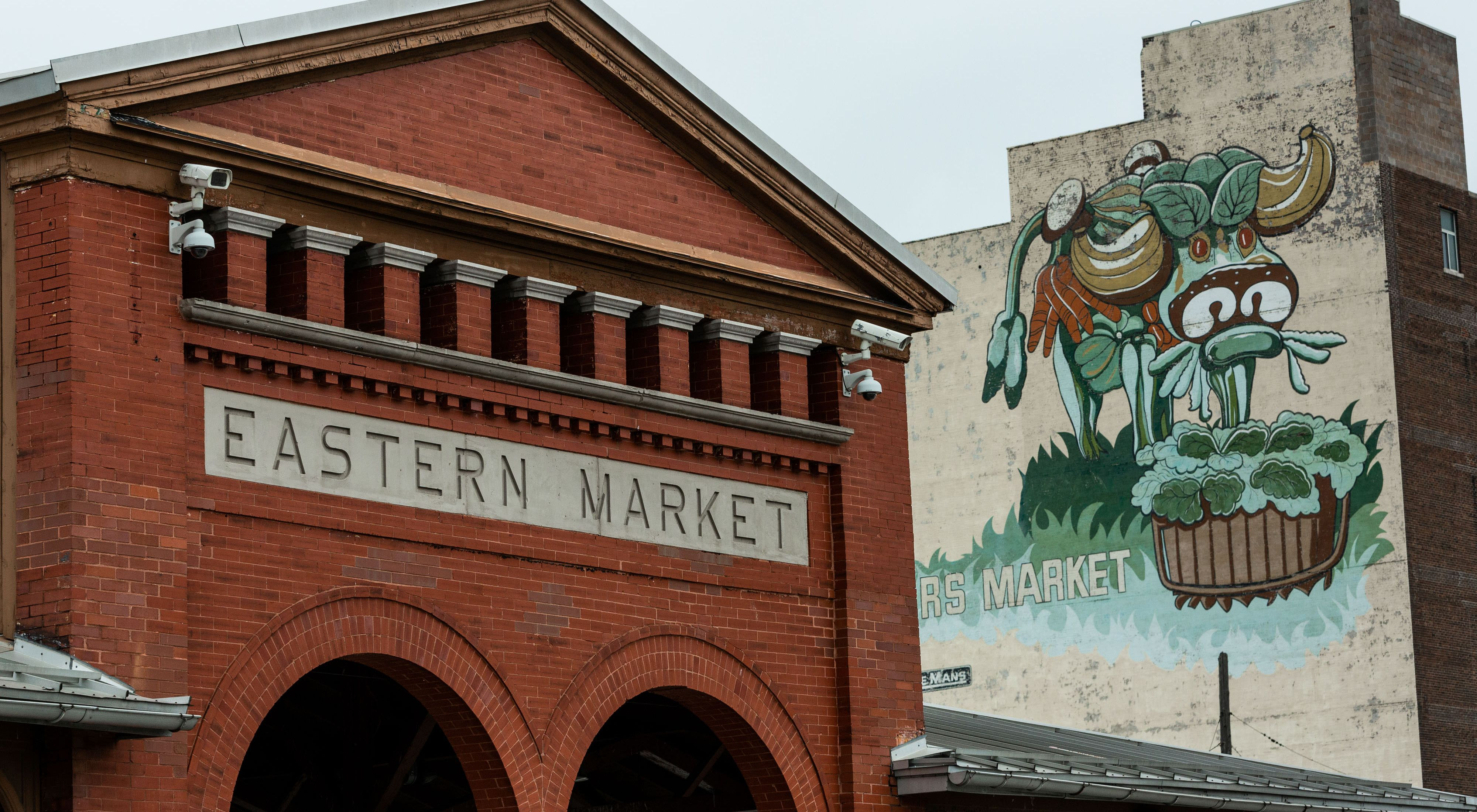 Red brick building for Eastern Market next to building with mural.