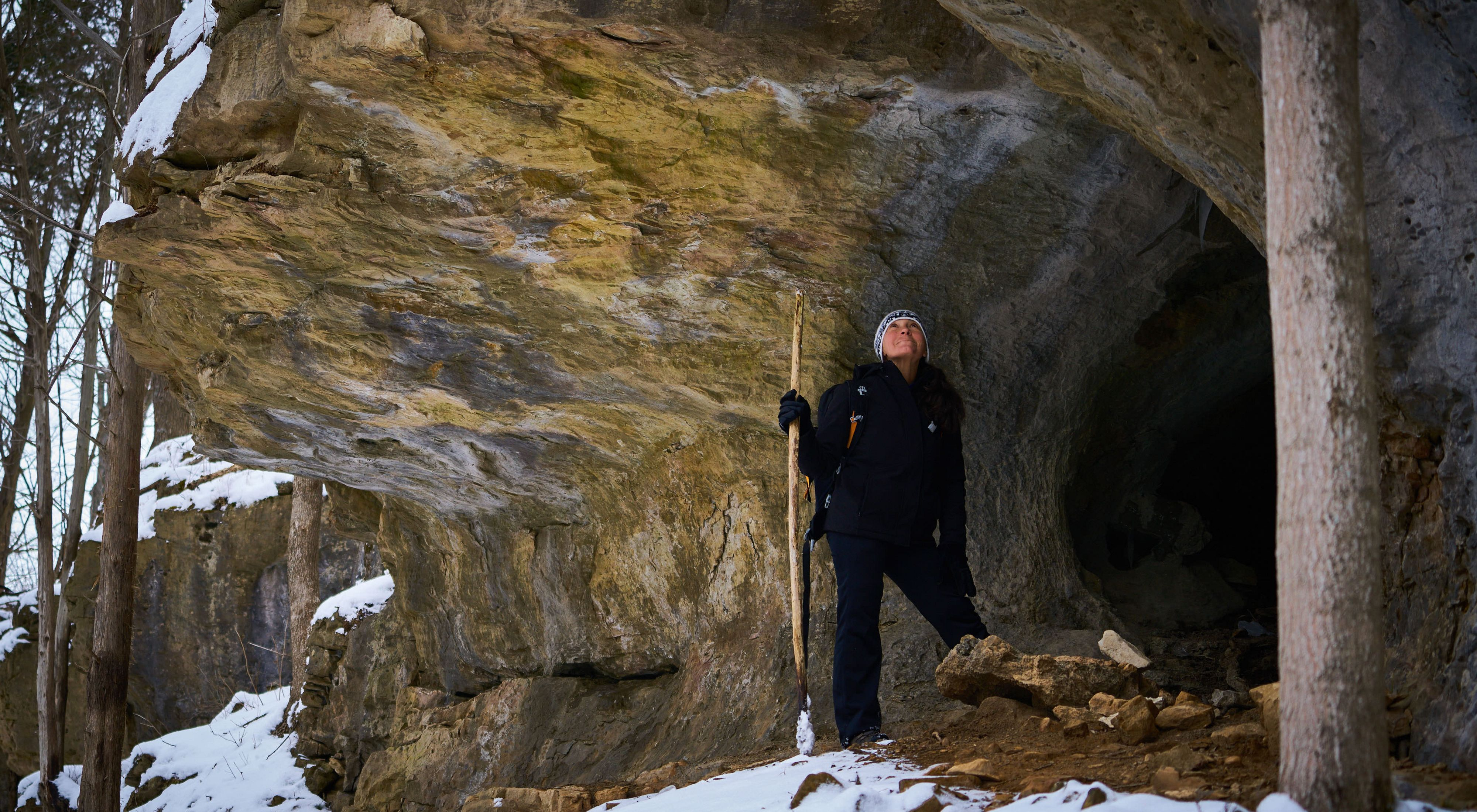 A woman dressed in black with a white winter hat, holds a walking sticks as she stands under a large rock overhang. Snow dots the rock and ground.
