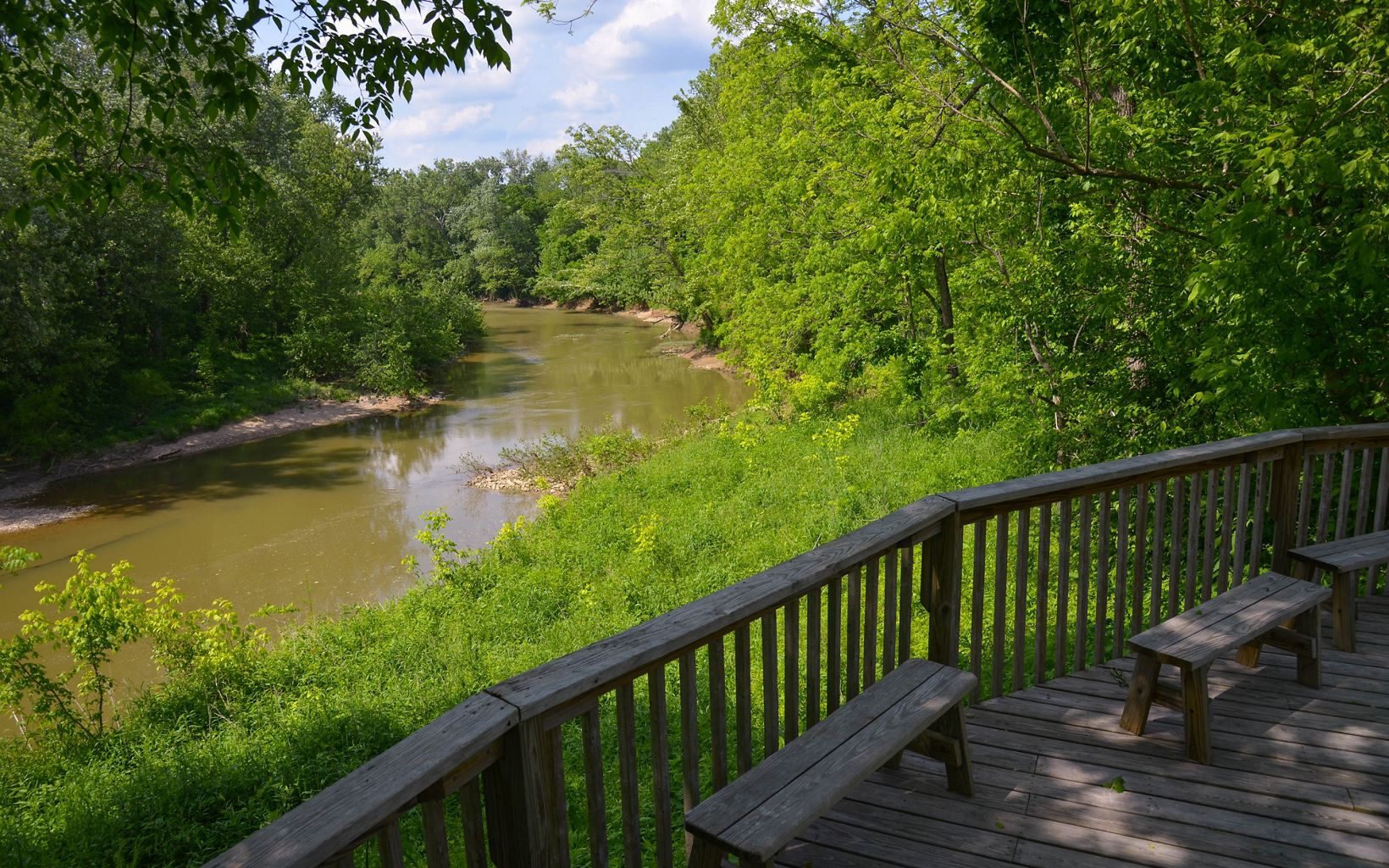 View from a wooden deck out over a slow-moving creek.