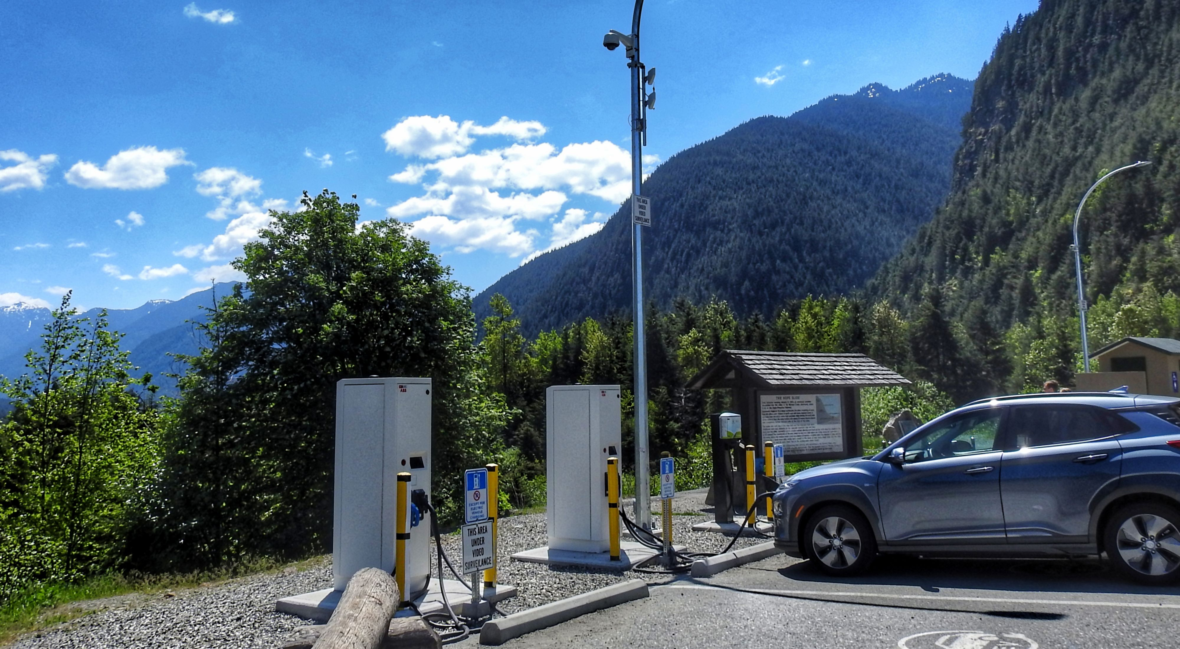 An electric vehicle is at a charging station at a scenic mountainous location in British Columbia.