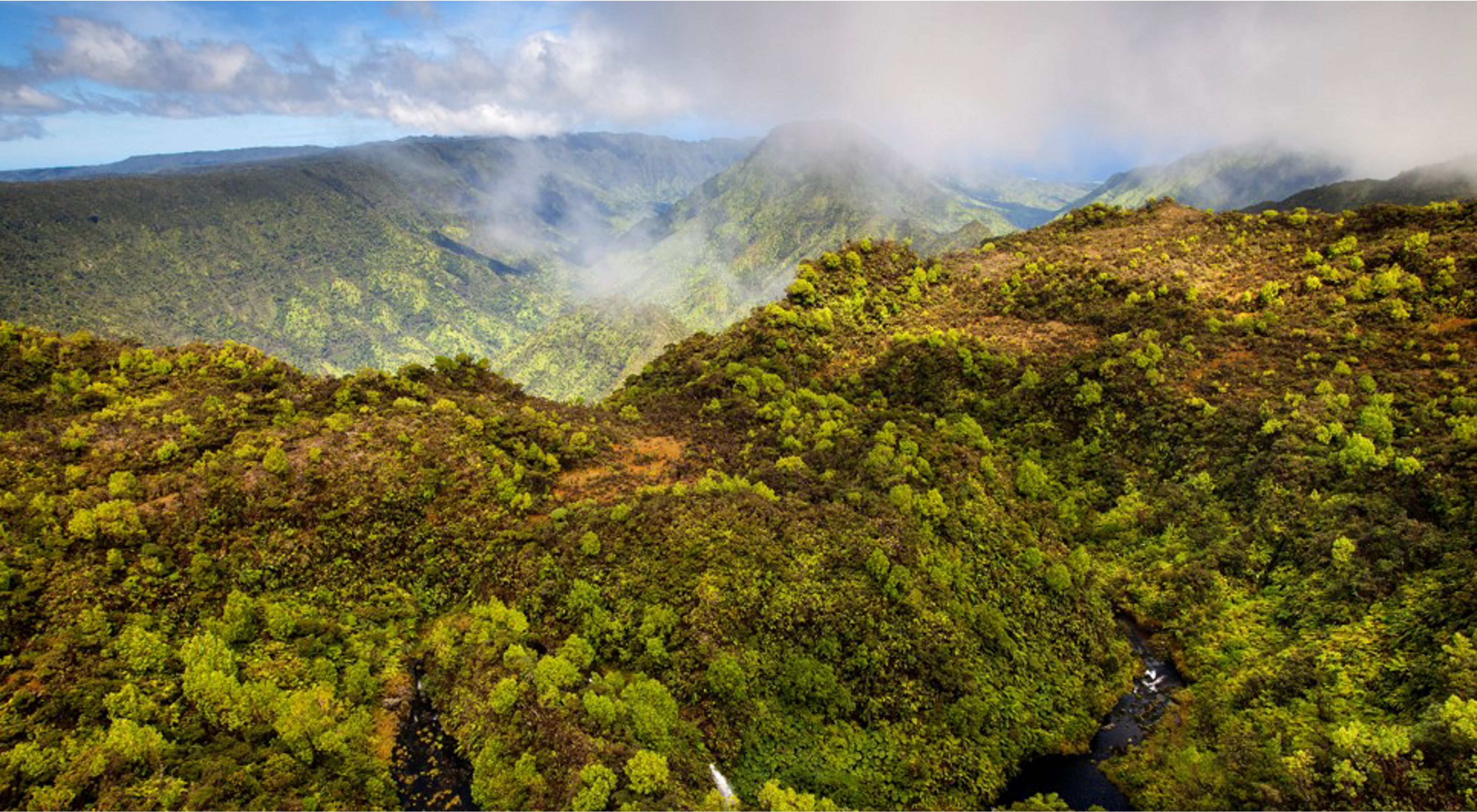 Lush, mixtures of green vegetated mountains with clouds misting the sky in the background.