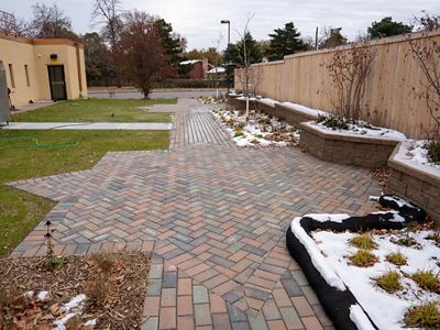 Plaza built with pervious pavers in a star shape lined with plants and a retaining wall.