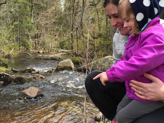 Eileen Bader Hall and her daughter watch as alewives migrate in a newly-restored stream in Maine.