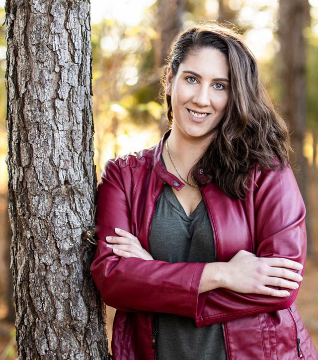 Headshot of Land Protection Director Elizabeth Carter. A smiling, dark haired woman wearing a gray top and red leather jacket leans again a tree.