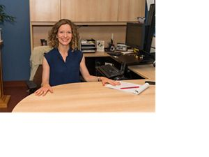 Elizabeth smiles at the camera seated at her desk with palms on the desk, computer and credenza in the background
