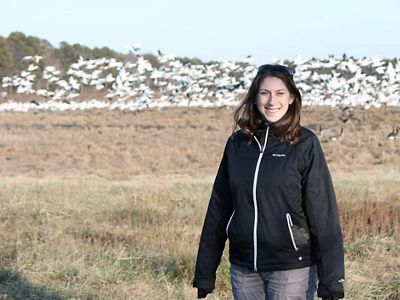 Emily Myron in a field with a large flock of white birds in the background.