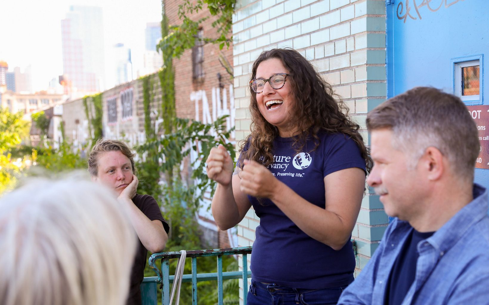 A woman wearing a blue t-shirt with The Nature Conservancy name and logo on it talks with a crowd. The woman is at the right side of the image, has brown curly hair, and wears glasses.