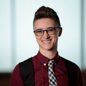 A person wearing glasses, maroon shirt and tie.
