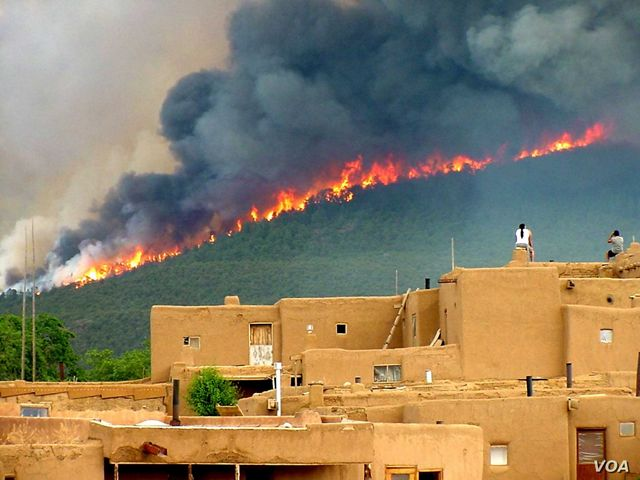 People watch the wildfire from their rooftops at the Taos Pueblo in New Mexico.