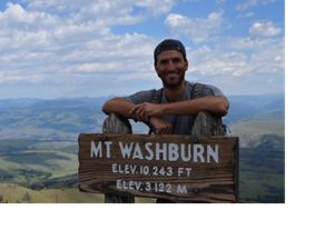 "Man standing on a mountain behind a ""Mt Washburn"" sign"