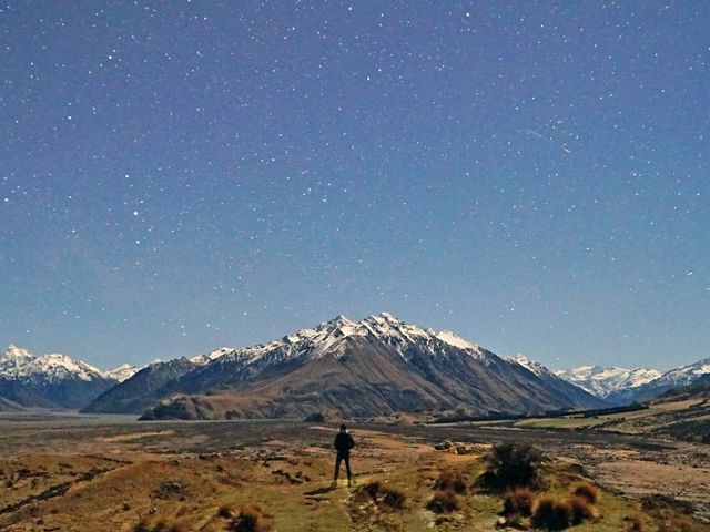 man looks at snowcapped mountains, grassland and stars