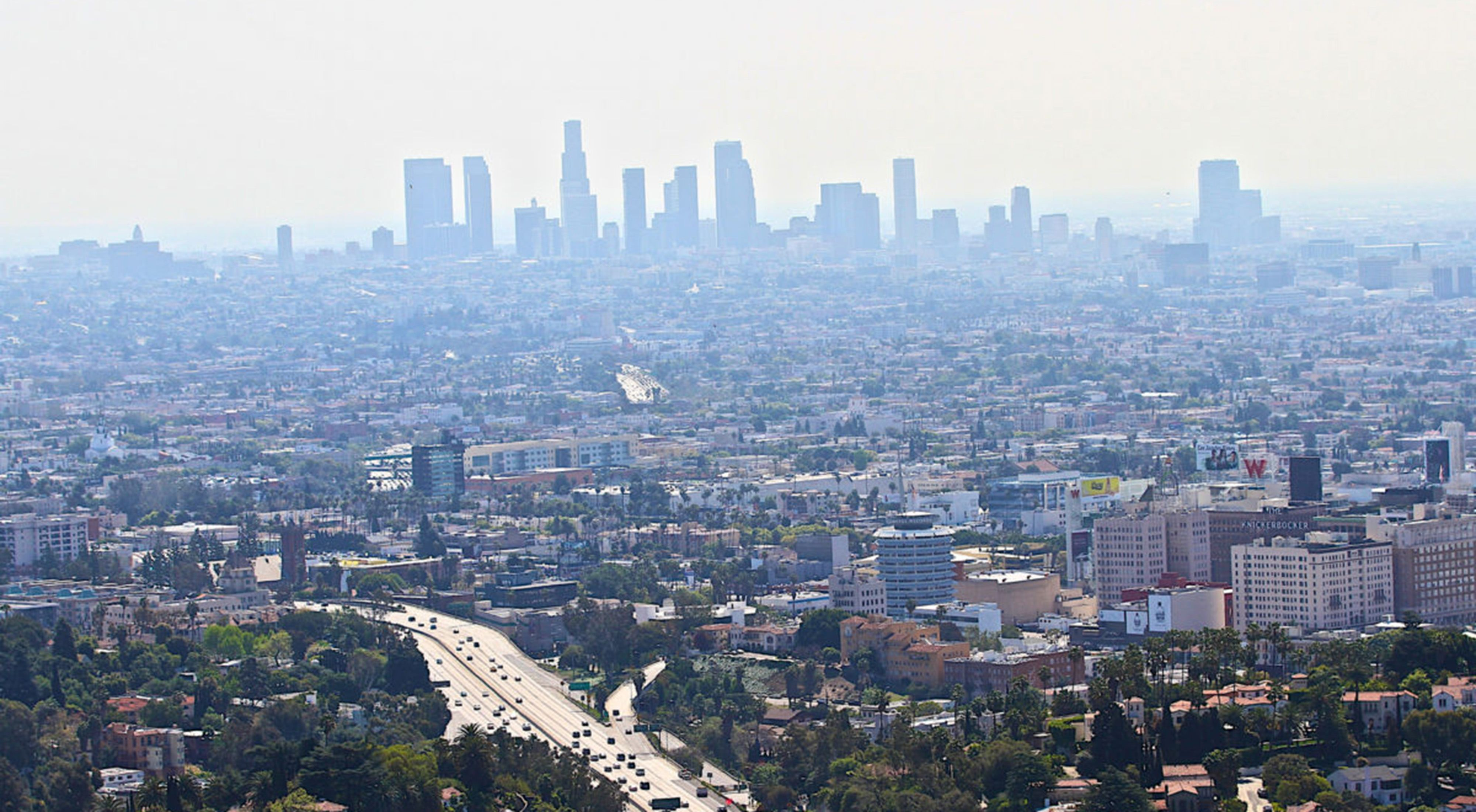 An aerial view of a highway and a large city skyline with smog