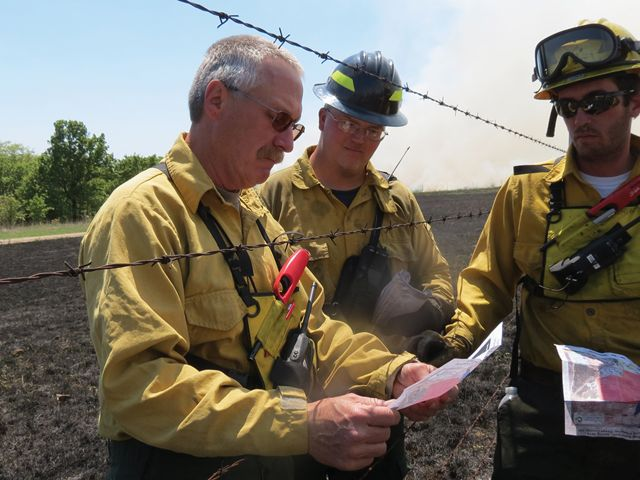 Three men standing across a fence line planning a prescribed fire.