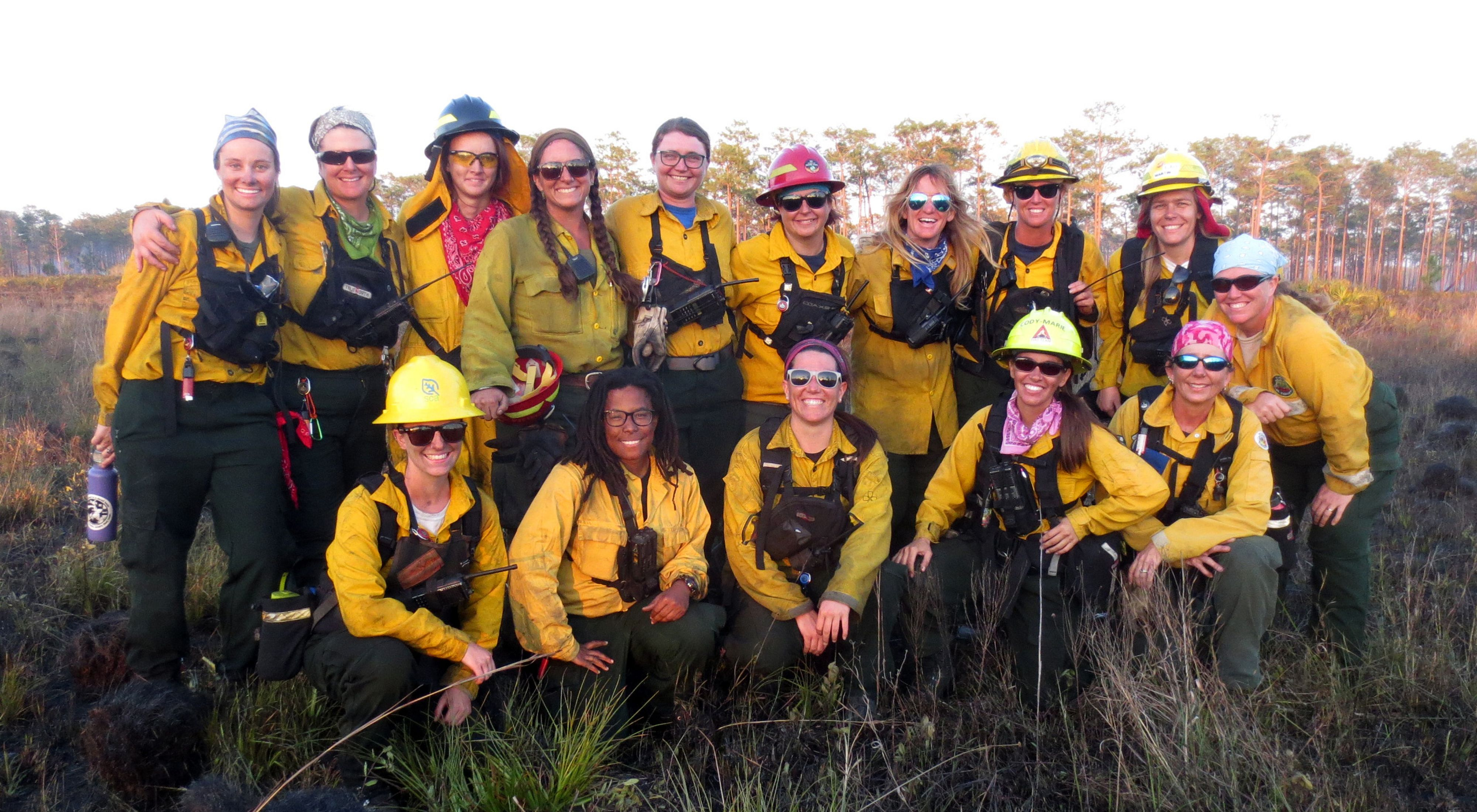 A group of about 15 smiling women in fire gear.