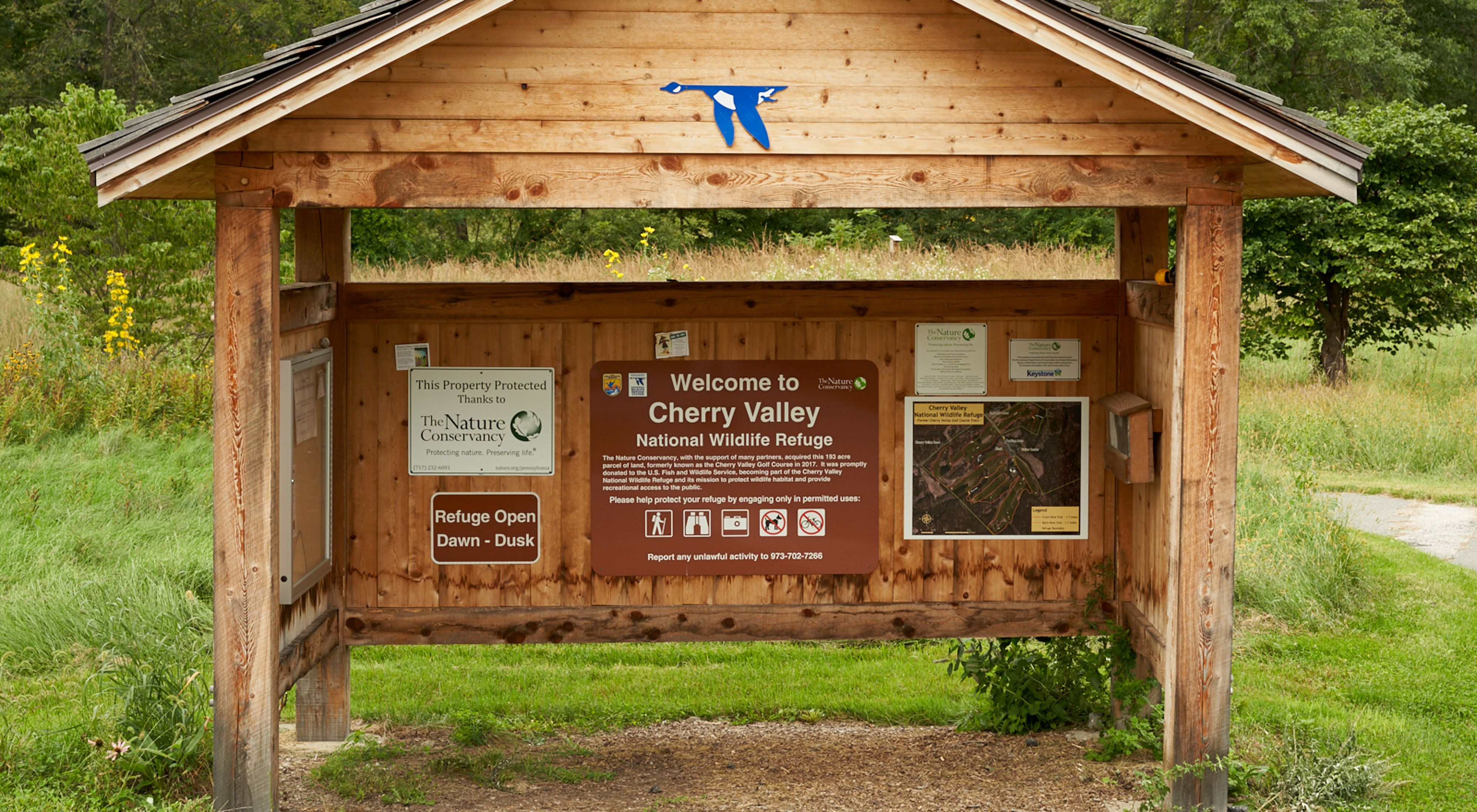 A wooden kiosk welcome visitors to Cherry Valley. The rear wall of the covered kiosk is covered with signs and maps providing visitor information.
