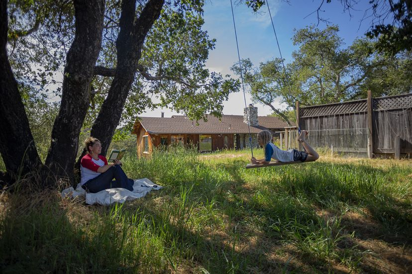 Scientist Heather Tallis sits under a tree at her house in California facing her son on a swing.