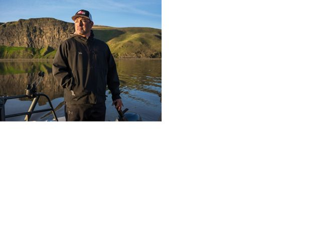 Portrait of Toby Wyatt standing on his boat on the Snake River