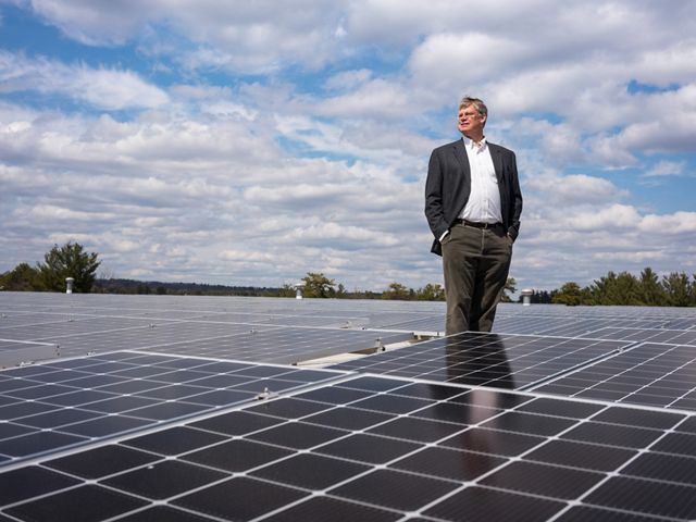 David Worthen stands among solar panels on the roof of Worthen Industries.