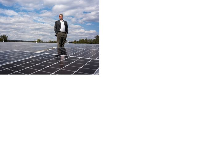 David Worthen, owner of Worthen Industries in Nashua, N.H., stands between more than 2700 solar panels installed on the roof of his adhesive manufacturing plant. Last summer, David invited New Hampshire's governor to tour Worthen Industries and hosted a roundtable discussion about investing more money in renewables in the state.
