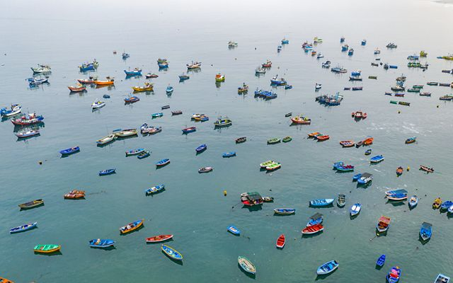 an aerial view of small, colorful fishing boats dotting the ocean