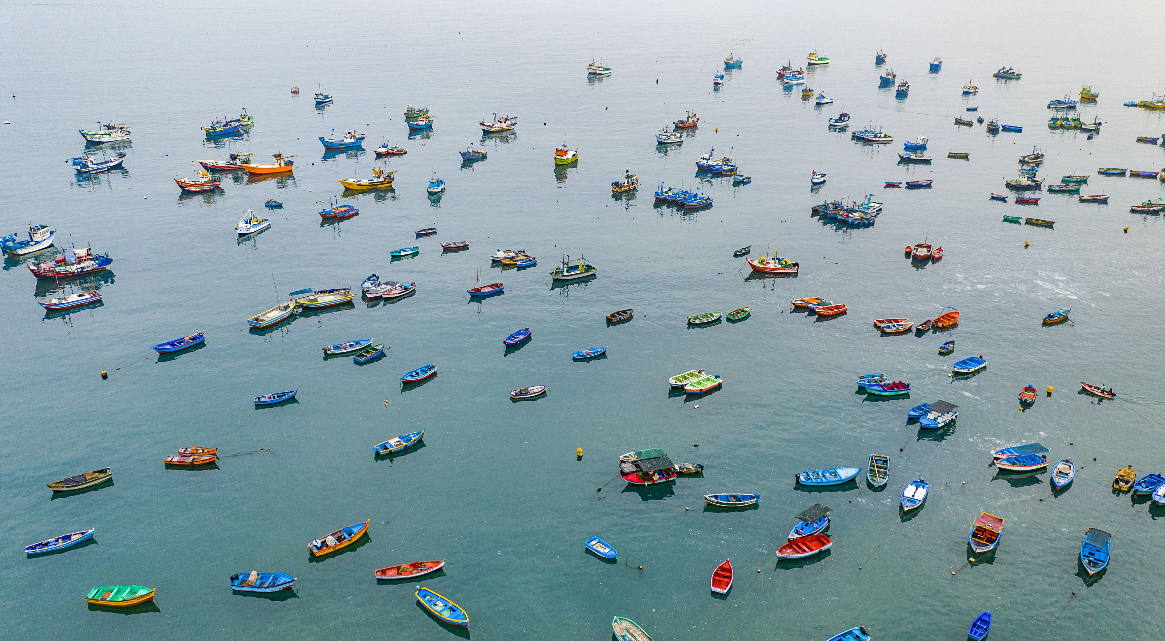 Colorful small boats are anchored in calm water