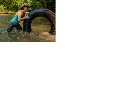 A woman removes a tire from a river