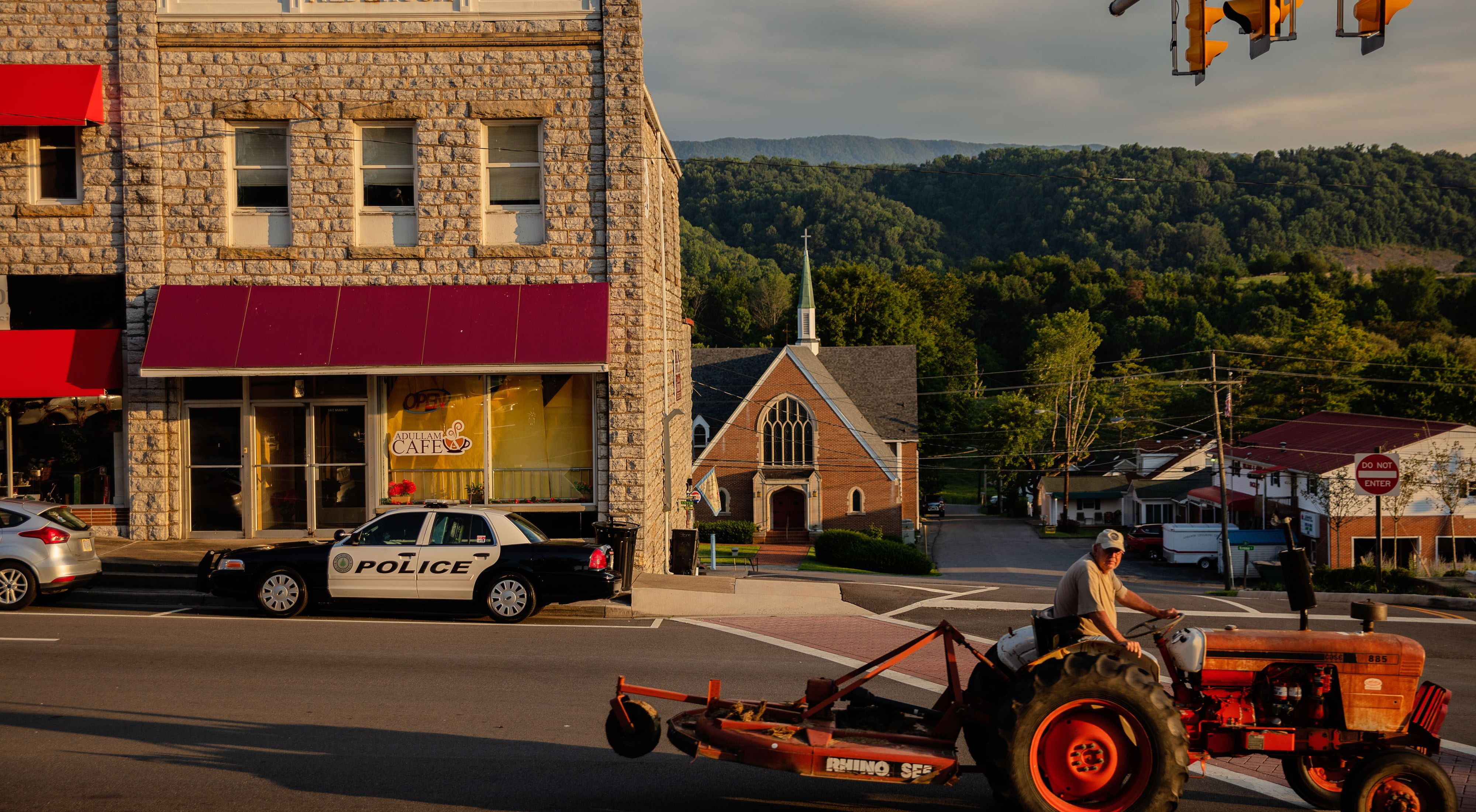 Street scene in St. Paul, VA. A red tractor drives past stone clad storefront. A police car is parked on the street. A church and other buildings are visible with a tall mountain in the background.