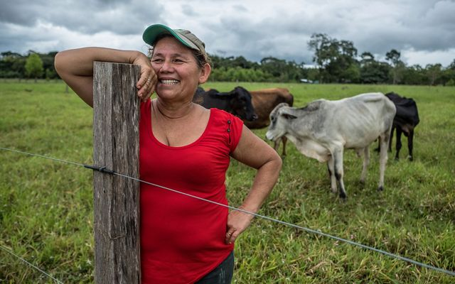 Mercedes Murillo smiles as she leans on a post on her ranch