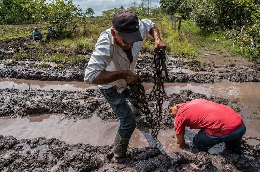 Edilson Ortiz Arango uses towing chains to extract his tractor from deep mud