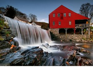 a small waterfall near an old red mill building