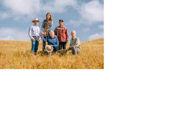 Five people pose with pitchfork on yellow grassland hills with blue sky