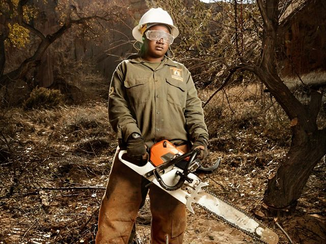 A young black woman in protective clothing with safety glasses and helmet, holding a chainsaw and looking at the camera.