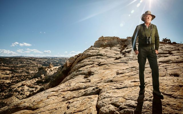 John Spence stands on a rocky outcrop under blue skies.