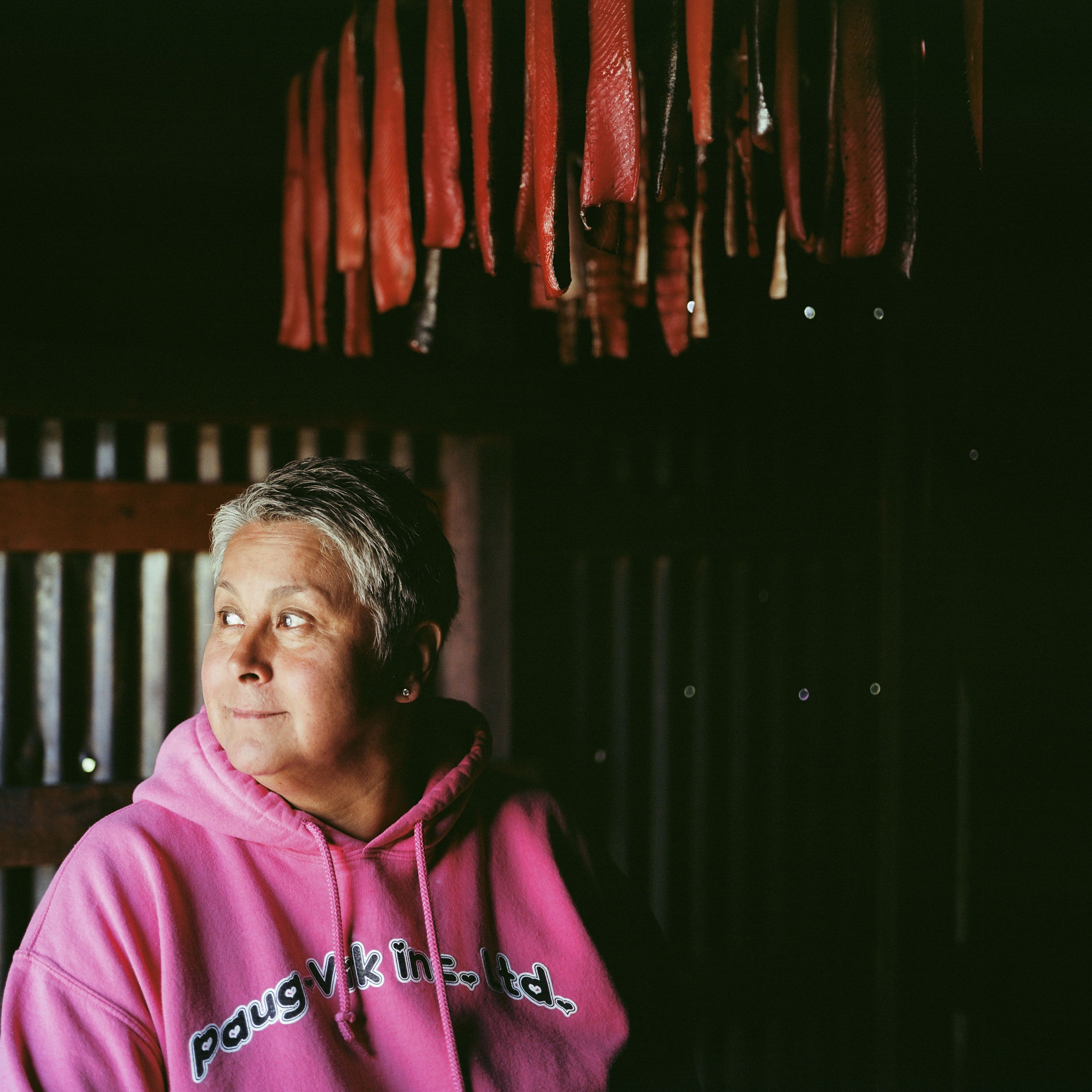 woman in sweatshirt below hanging red strips of fish