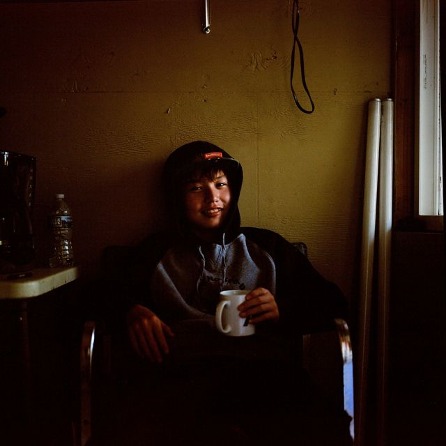 young boy in hoodie sits indoors by window with mug, looks at camera