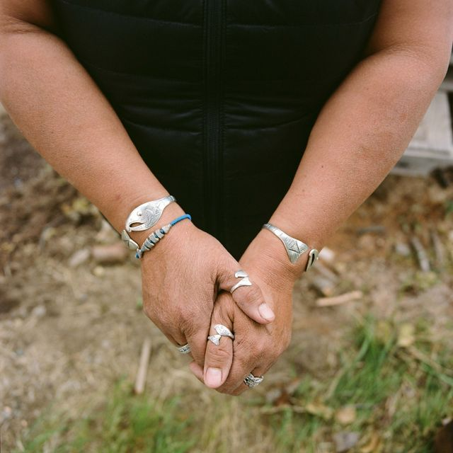 close up of hands and wrists with multiple silver rings and bracelets in the shape of fish