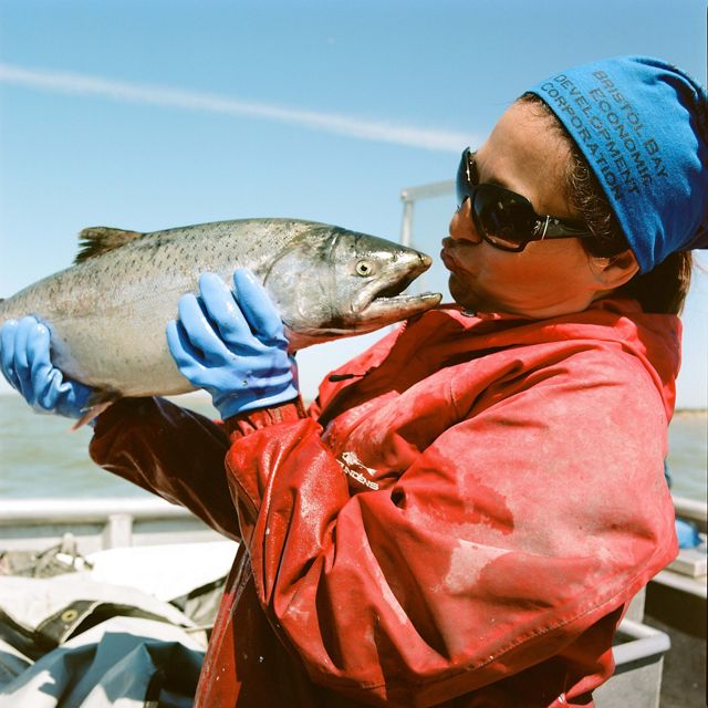 Fisher in red jacket holds silver-colored fish up to her face and almost kisses it. In boat on water