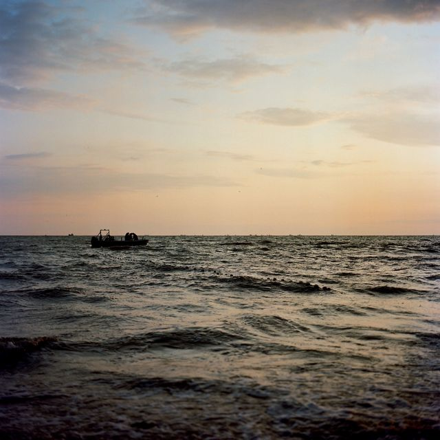 a small boat is silhouetted on water with waves, sky is sunset colored, no land on horizon
