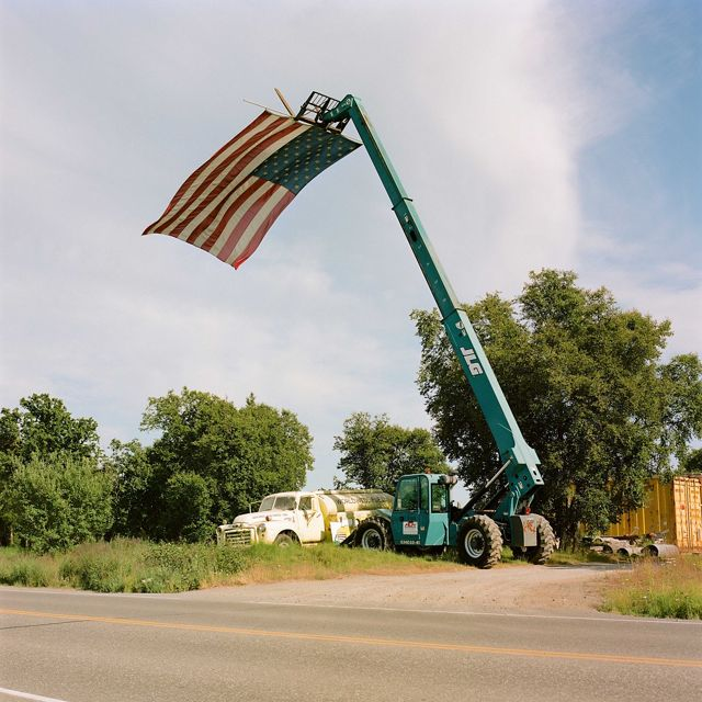 by the side of a road, a crane holds an American flag vertically that blows in the window below the top of the crane