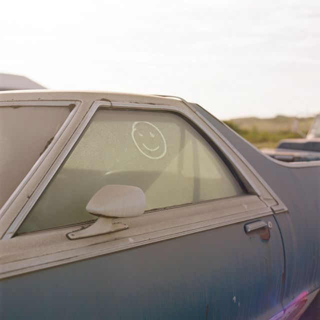 close up of a gray-blue older car covered in brown dust, a smiley face drawn in the window dust