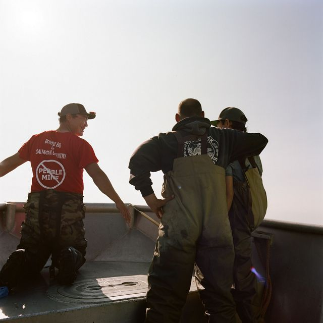 Two men and one boy stand in waders on the edge of a boat, backs turned, one with an arm around the boy.
