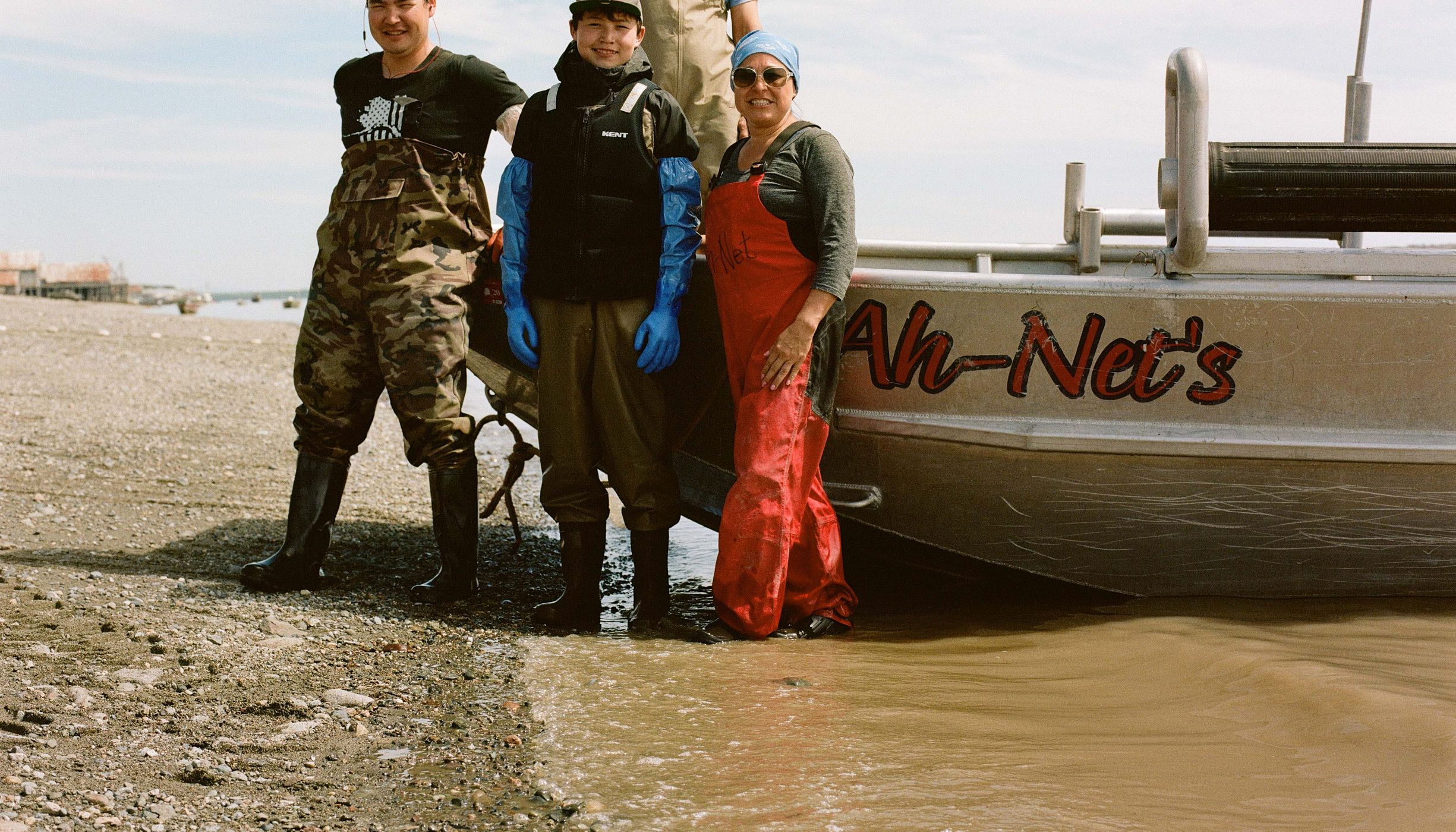 4 people in waders stand beside boat pulled onto rocky