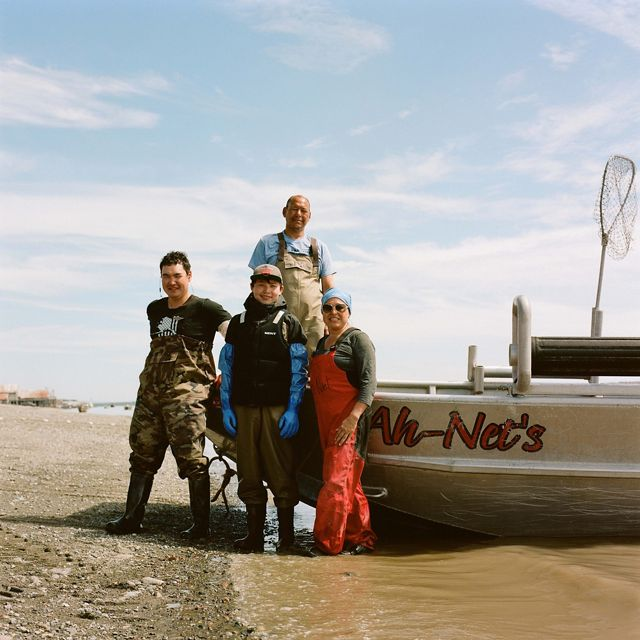4 people in waders stand beside boat pulled onto rocky shore, smiling for picture