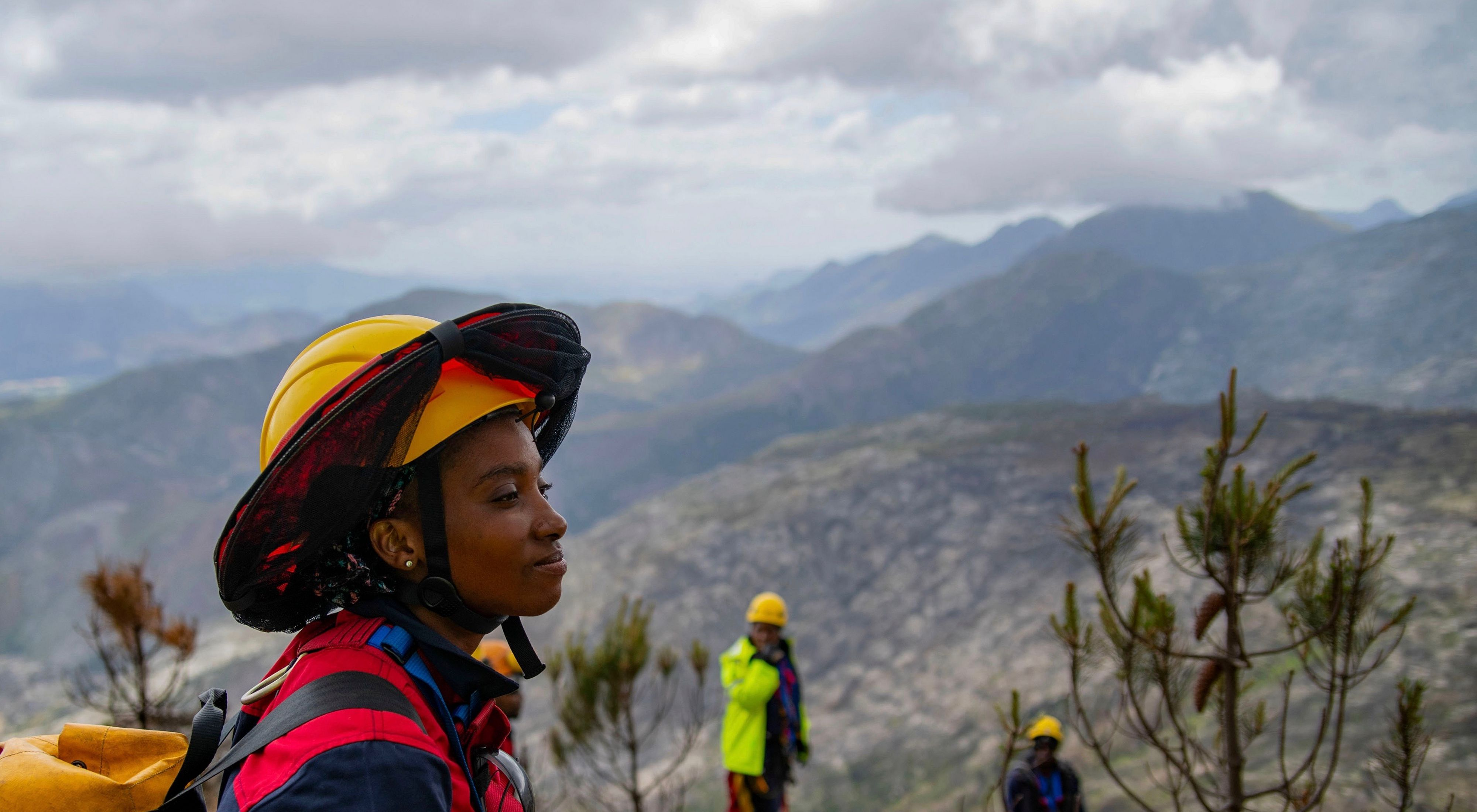 A person overlooking a mountain with a yellow helmet and backpack on.