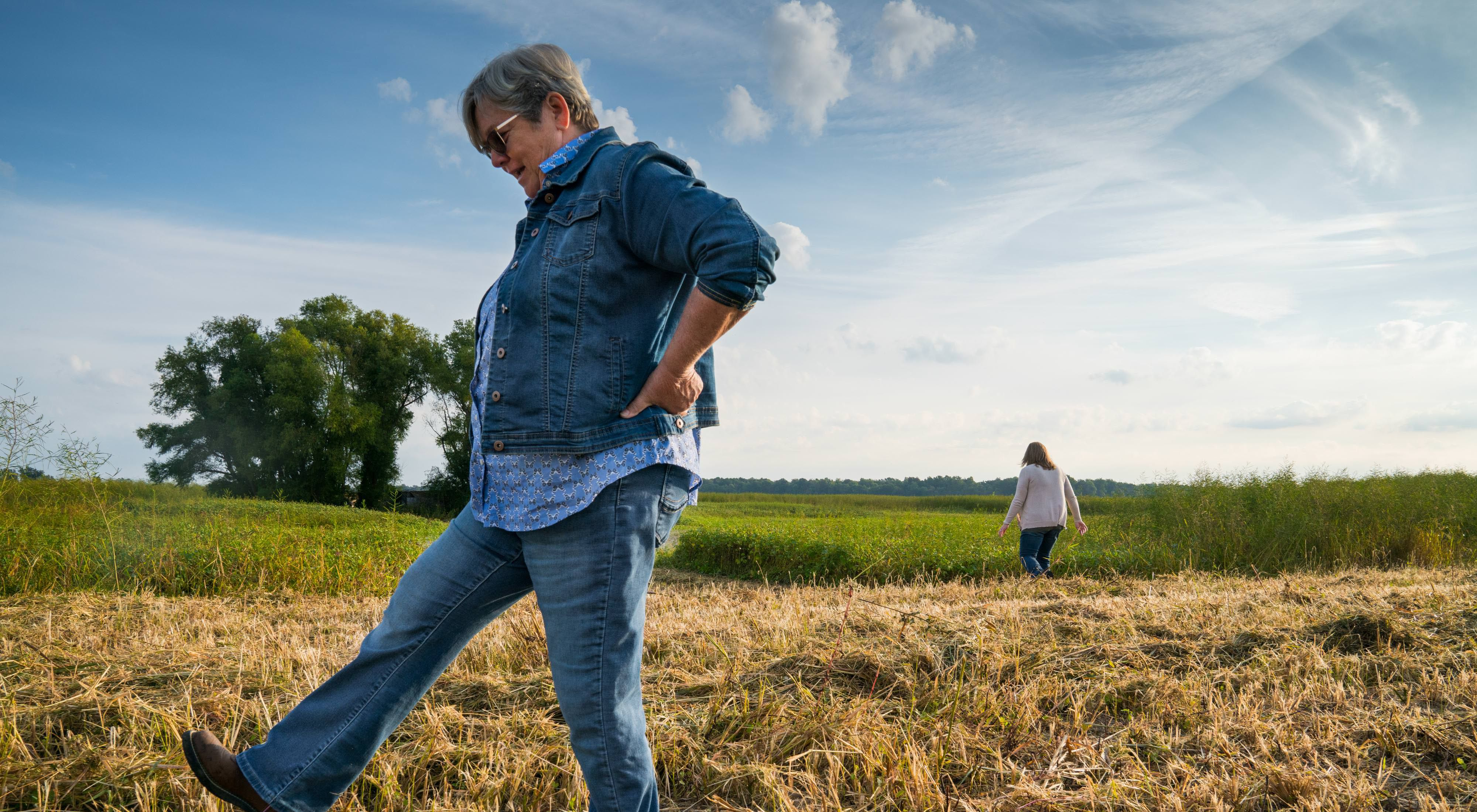 A woman kicks at the grass on her family's farm